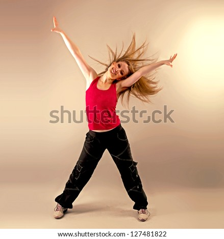 Young woman dancing fitness with disheveled hair and raised hands in studio