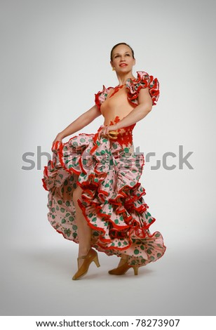 Young woman dancing flamenco with castanets on gray background