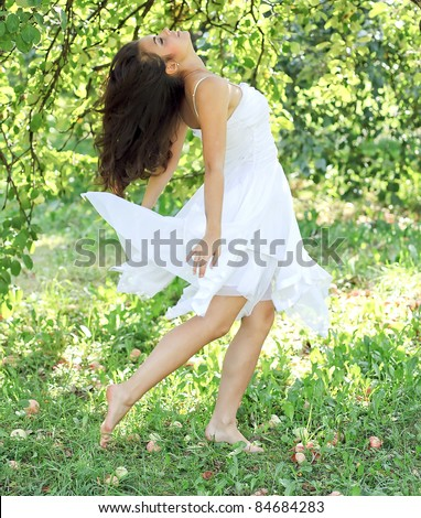 young woman dancing in the morning bright spring orchard