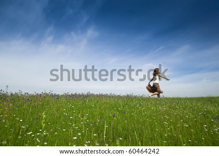 Young woman dancing on a beautiful green meadow