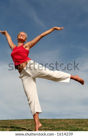 Young woman dancing on grass - stock photo