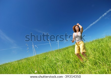 Young woman dancing on the green field - stock photo