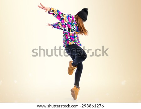 Young woman dancing street dance over ocher background