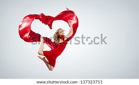 Stock Photo Young woman dancing with red fabric in studio and heart symbol