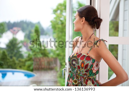 Young woman daydreaming while standing near door
