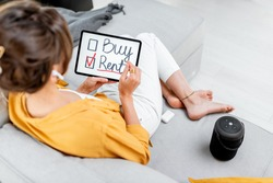 Young woman decides between buying or renting real estate, holding digital tablet indoors. Concept of choosing the right housing solution