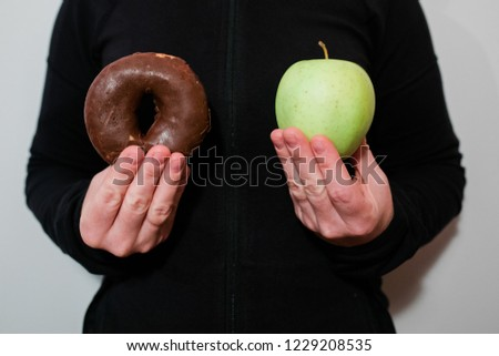 Young woman deciding between donut and apple, healthy and unhealthy eating #1229208535