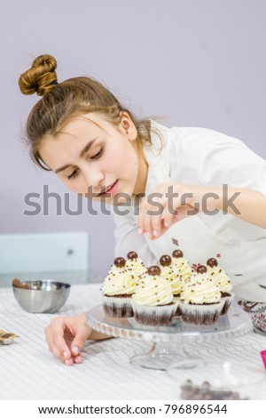 Young woman decorates cupcakes #796896544