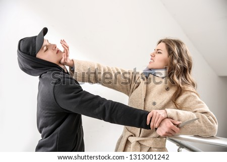 Young woman defending herself from thief in stairway Stock photo ©