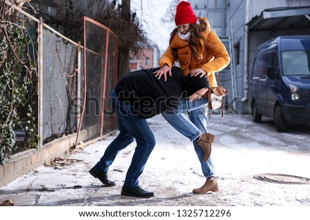 Young woman defending herself from thief outdoors Stock photo ©