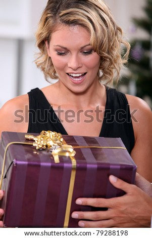 Young woman delighted to receive a prettily wrapped Christmas present