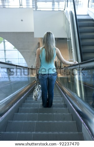 young woman descending an escalator in the airport