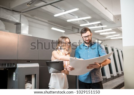Young woman designer and print operator working together with paper print standing at the print manufacturing