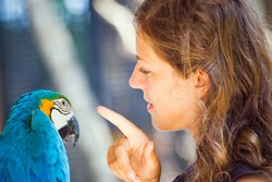 Young woman discussion with parrot in zoo