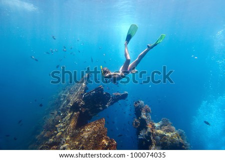 Young woman diving on a breath hold and fining in blue transparent sea near wreck USAT Liberty, Tulamben, Indonesia