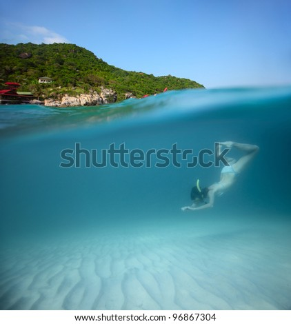Young woman diving on a breath hold in a clear tropical sea with green island on the background