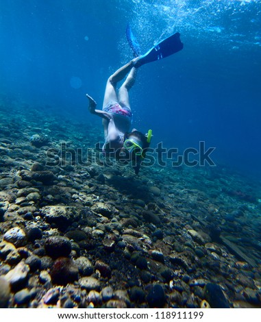 Young woman diving on a breath hold in a tropical sea