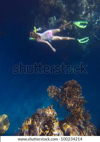 Young woman diving on a breath hold near a vivid coral reef wall