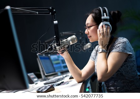 young woman dj works in modern broadcast studio
