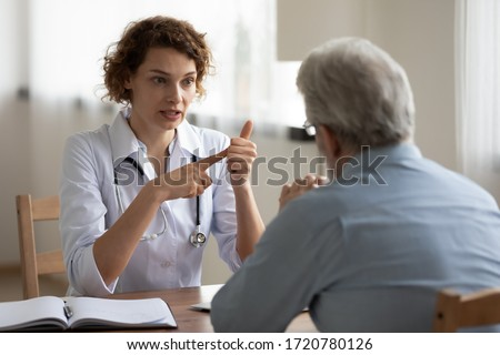Young woman doctor consulting senior male patient at visit in hospital giving healthcare advice. Female physician prescribing geriatric disease treatment speaking to older man. Elderly medical care.