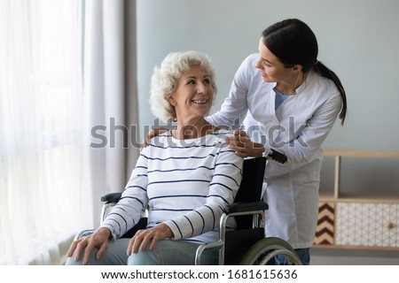 Young woman doctor give help support handicapped old lady patient sitting in wheelchair, female caregiver or nurse assist take care of smiling senior disabled grandma, elderly healthcare concept