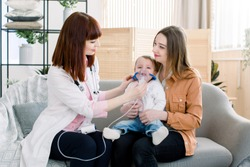 Young woman doctor helping to little baby girl with nebulizer mask, showing how to make inhalation therapy for her mother