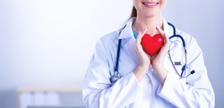 Young woman doctor holding a red heart, isolated on white background