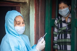 Young woman doctor in PPE protective mask and gloves holding a syringe and coronavirus vaccine, standing with village women explaining importance of corona virus vaccine.