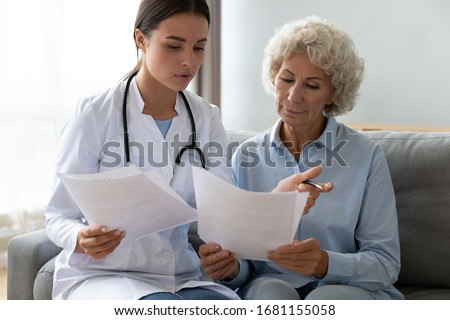 Young woman doctor visit senior old lady patient at home explain medical documents insurance, attentive female give consultation close sign healthcare agreement with elderly grandmother at home