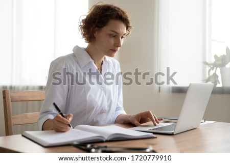 Young woman doctor working on laptop taking notes at workplace. Female physician writing in notebook using computer sitting at desk. Professional medic therapist everyday routine in hospital office.