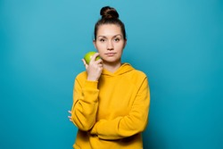 young woman does not express any emotions and holds an apple near her face