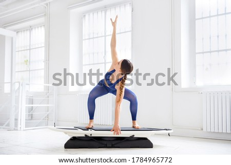 Young woman doing a surfset barrel squat pose during a workout in a high key gym in a health and fitness or active lifestyle concept with copyspace