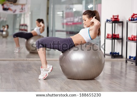 Young woman doing abs crunches with a ball in the gym