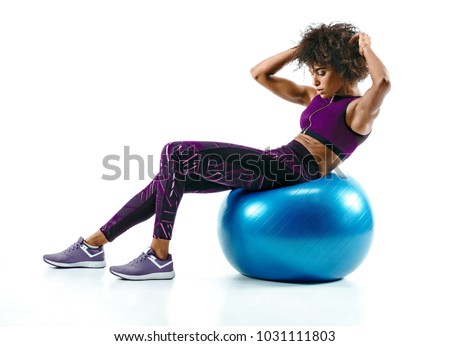 Young woman doing abs exercise on fitness ball. Photo of african girl in silhouette on white background. Fitness and healthy lifestyle concept
