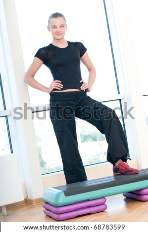 Young woman doing aerobic exercises at the sport gym