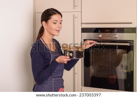 Young woman doing baking at home placing a cake in the oven to cook reaching out with her hand to open the oven door while holding a baking tin stock photo