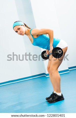 young woman doing body-building in the Gym, live a healthy life
