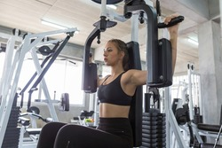 Young woman doing exercise on a chest machine fly in the gym. Women wear sportswear flexing arm muscles on chest machine fly in gym