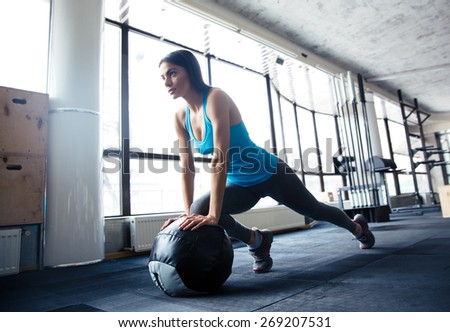 Young woman doing exercise with fit ball at gym #269207531