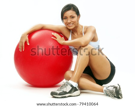 Young Woman doing fitness exercise with a red ball. Young latin woman holding a fitness gym red ball.