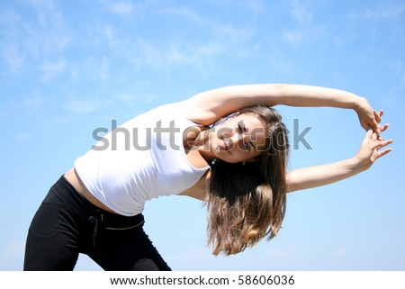 Young woman doing fitness exercises against blue sky
