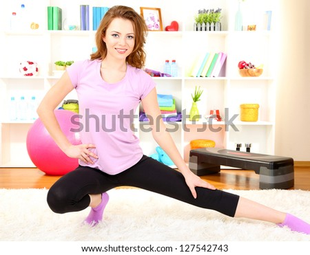 Young woman doing fitness exercises at home - stock photo