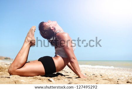 Young woman doing full cobra yoga pose at the deserted sea coast