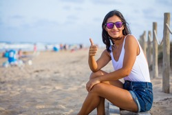 young woman doing gesture ok on the beach