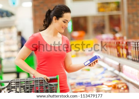 young woman doing grocery shopping in supermarket - stock photo