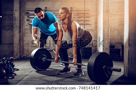 Young woman doing hard exercise at the gym with a personal trainer.