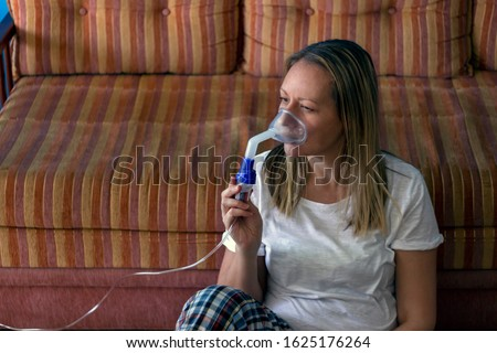 Young woman doing inhalation with nebulizer at home.Female holding a mask nebulizer inhaling fumes spray the medication into your lungs sick patient.Young woman's face inhaling through inhaler mask.