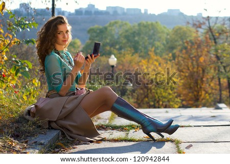 Young woman doing makeup sitting on road in the park