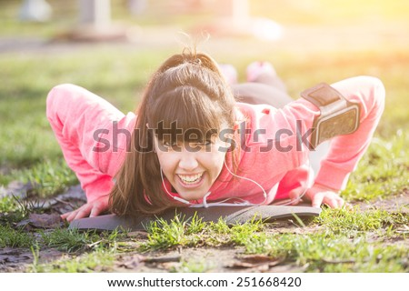 Young Woman Doing Push-Ups Exercises at Park. She is also Listening Music with Earphones. The girl is using a Fitness Mat. Some People on Background doing Exercises too.