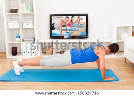 Young Woman Doing Pushup In Front Of Television #158829716